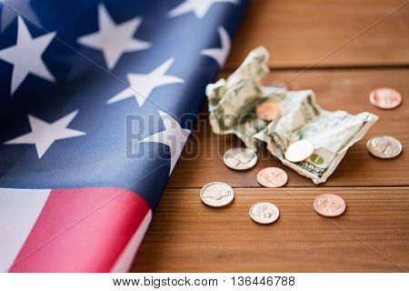 budget, money, finance, financial crisis and nationalism concept - close up of american flag and cent coins with crumpled dollar banknote on wood