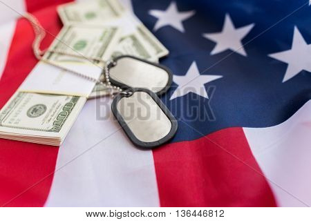 military forces, recruitment, financing and national service concept - close up of american flag, dollar money and military badges