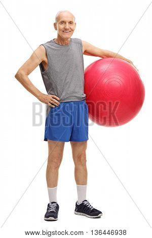 Full length portrait of an active senior man holding a pink fitness ball isolated on white background