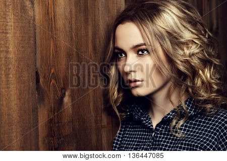 Casual teen girl standing by a wooden wall. Youth style, fashion.
