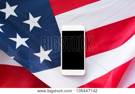 technology, american independence day, patriotism and nationalism concept - close up of smartphone with black blank screen on american flag