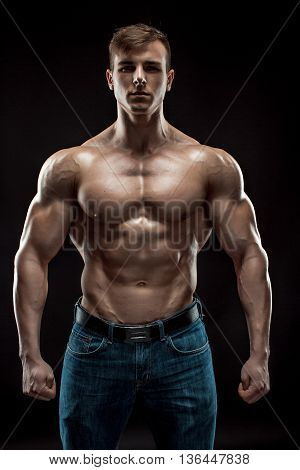 Muscular bodybuilder guy doing posing over black background. Naked torso in jeans. He looks into the camera