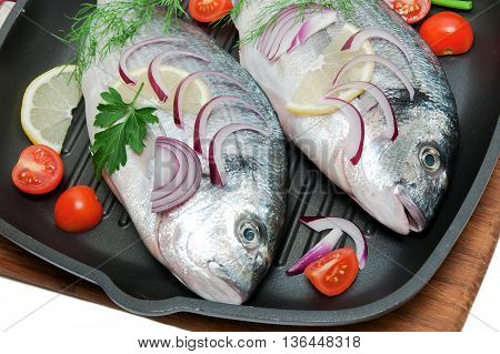 Dorado fish vegetables and herbs in a pan. horizontal photo.