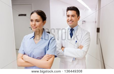 healthcare, profession, people and medicine concept - smiling doctor in white coat and nurse at hospital