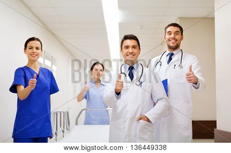 clinic, profession, people, health care and medicine concept - group of happy medics or doctors with gurney showing thumbs up at hospital corridor