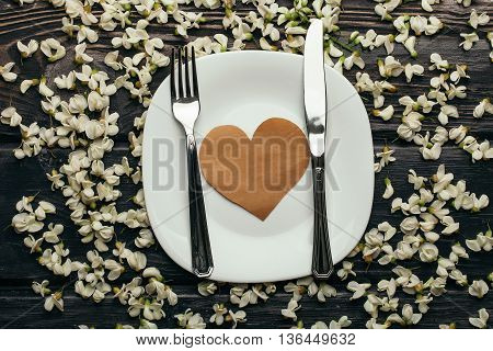 Plate with heart note fork and knife in white acacia blossoming flower petals decorative frame on dark wooden background