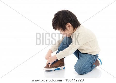 little asian boy tying his shoes isolated in white background