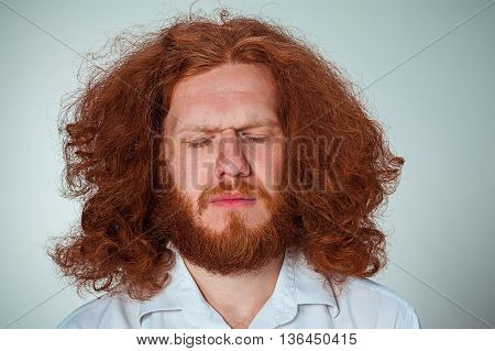 The young man with long red hair closing both eyes
