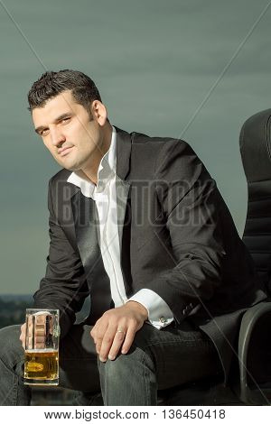 handsome male businessman with courageous face in black formal jacket and white shirt holding beer glass sitting on leather office arm chair outdoor on city background