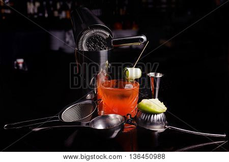 Red cocktail drink with ice. stainless steel cocktail bar tools and shaker.