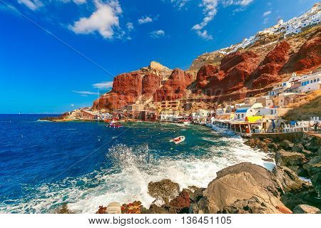 The waves beat against the rocks on a sunny summer day at Old port Ammoudi of Oia village at Santorini island in Aegean sea, Greece