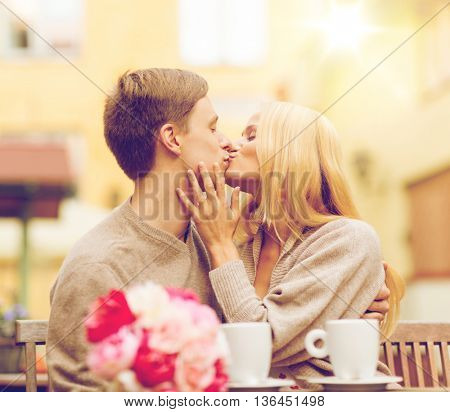 summer holidays, love, travel, tourism, relationship and dating concept - romantic happy couple kissing in the cafe