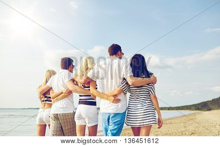 summer, holidays, sea, tourism and people concept - group of smiling friends hugging and walking on beach from back