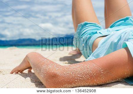 young beautifull girl lies on the white sand of tropical beach under cloudy sky at sunny day
