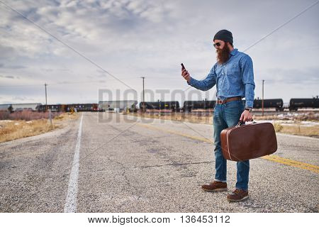 lost bearded hitch hiker with smart phone looking for directions on desolate nevada road
