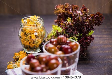 many wet raw ripe gooseberry in glass with dry calendula