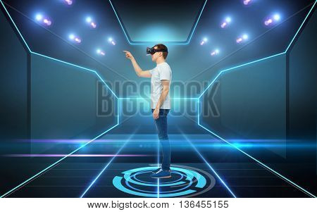 3d technology, virtual reality, cyberspace and people concept - young man with virtual reality headset or 3d glasses playing game over black background and laser light