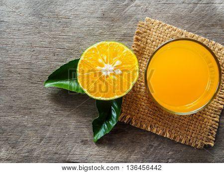 Orange fruit and orange juice of top view on wooden background