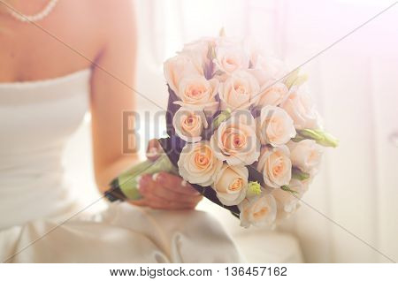 peach roses for wedding bouquet at bride's hands