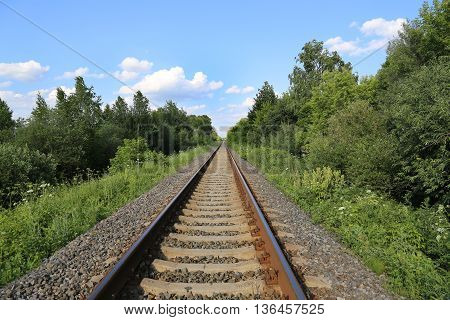 Summer landscape with railway track and blue sky