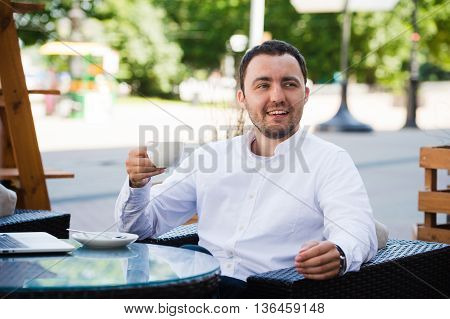 Confident successful businessman in suit enjoying a cup of coffee while having work break lunch in modern restaurant, young intelligent man or entrepreneur relaxing in outdoors cafe looking pensive.