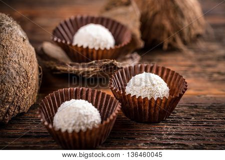 White chocolate candy coconut truffles on wooden background