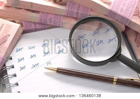 Abstract pile of money on top of ring bound book with mark showing amount of counted money