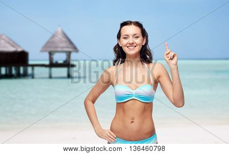 people, travel, tourism, swimwear and summer holidays concept - happy young woman in bikini swimsuit pointing finger to something imaginary over exotic tropical beach with bungalow in sea background