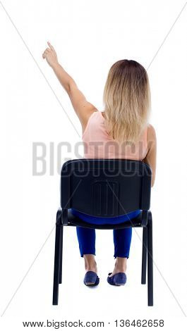 back view of young beautiful  woman sitting on chair and pointing.  girl  watching. Rear view people collection.  backside view of person.  girl is sitting on an office chair and shows up