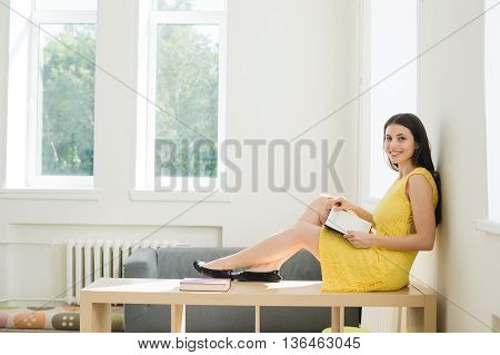 Female student preparing for exam. Teenager girl studying sitting on a rack home in the living room or at school library.