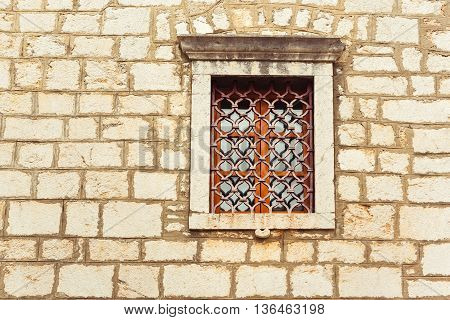 old window on old wall fortified church