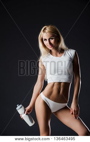 Fitness lady holding a bottle of water over dark studio background.