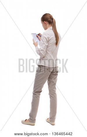 back view of  stands woman takes notes in a notebook. Rear view people collection.  backside view of person.  Isolated over white background. Girl with long hair in a white jacket writing in notebook