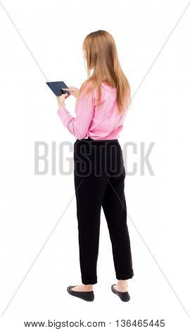 back view of standing young beautiful  girl with tablet computer in the hands of. girl  watching. The girl office worker in black trousers finger of the left hand presses the screen tablet PC.
