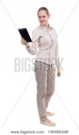 front view of standing young beautiful  girl with tablet computer in hands of. girl  watching. Rear view people collection. Isolated over white background. girl in white jacket smiling read e-books