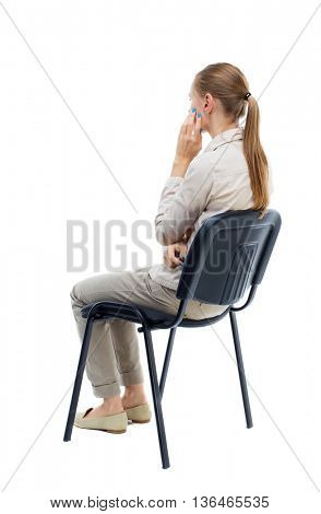 back view of young beautiful woman sitting on chair. Rear view people collection.  backside view of person. Girl with long hair in a white jacket is sitting on chair resting his hand on cheek