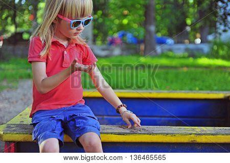Boy sitting in the sandbox on summer