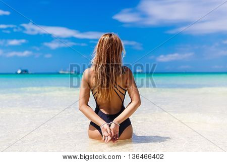 Happy beautiful young girl back to the viewer on a tropical beach. Blue sea in the background. Summer vacation concept.