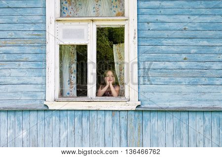 Sad bored little girl looking out the country house window leaning her face on her hands. Outside view