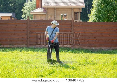 man mows the grass with a string trimmer