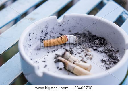 Cigarette stub in ashtray on iron table.