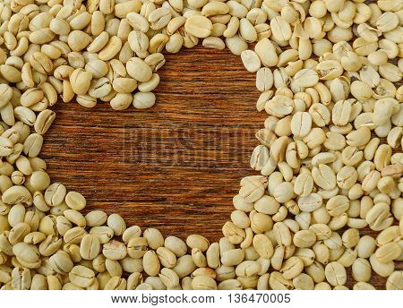 Coffee Beans Heart background Dark wooden desk top view.