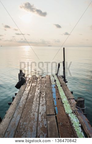 Wooden jetty bridge with seascape during sunrise at Ao Lung Dam beach in Samet island Thailand.