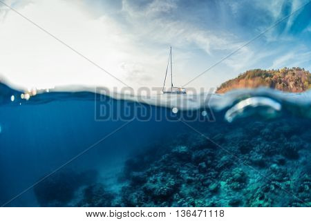 Split shot with hilly tropical terrain on the surface and reef underwater