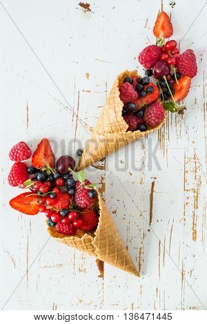 Selection of fresh berries in waffle cones, white wood