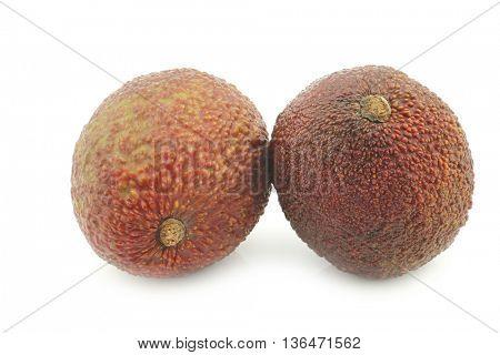two fresh eat ripe avocado's on a white background