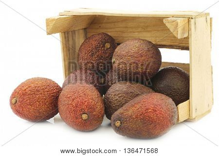 Eat ripe avocado's in a wooden crate on a white background