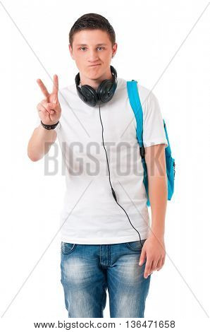 Happy teenage student boy showing victory sign, isolated over white background