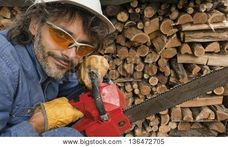 woodcutter worker with chainsaw looking at camera