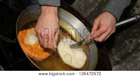 Two Large Pancakes Dipped In Hot Oil In An Aluminum Pot